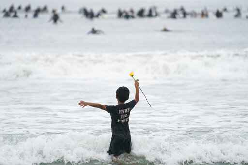 Nathan Rangel, 11, jumps in the water carrying a rose as surfers participate in a paddle out ceremony at