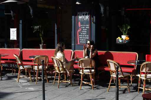Women sit on a terrace in Paris, Tuesday, June 2, 2020. Parisians who have been cooped up for months with take-out food and coffee will be able to savor their steaks tartare in the fresh air and cobbled streets of the City of Light once more -- albeit in smaller numbers. (AP Photo/Thibault Camus)