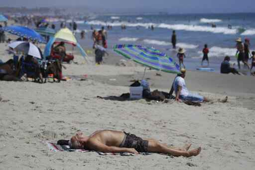 FILE - In this Sunday, July 12, 2020, file photo, a man lies on the beach amid the coronavirus pandemic in Santa Monica, Calif. California faces a heat wave Friday, Aug. 14, 2020, that could bring dangerously high temperatures throughout the state, along with the threat of wildfires and spreading coronavirus infections as people flock to beaches and recreation areas. (AP Photo/Marcio Jose Sanchez, File)