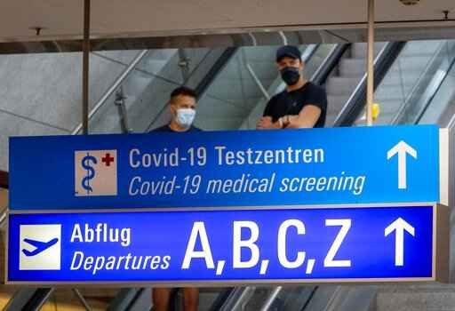 A sign recently fixed shows the way to the Covid-19 test center at the airport in Frankfurt, Germany, Saturday, Aug. 15, 2020. (AP Photo/Michael Probst)
