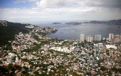 FILE - This Sept. 20, 2013 file photo shows an aerial view of the Pacific resort city of Acapulco, Mexico. Mexico's Pacific coast resort of Acapulco expressed hope Friday, Aug. 14, 2020, for a return of tourists, as the number of new coronavirus cases drop and the violence that drove travelers away slowly declines. (AP Photo/Eduardo Verdugo, File)