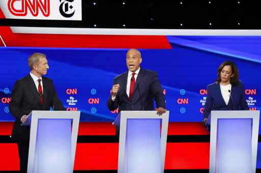 Democratic presidential candidate businessman Tom Steyer, left, and Sen. Kamala Harris, D-Calif., right, listen as Sen. Cory Booker, D-N.J., speaks during a Democratic presidential primary debate hosted by CNN/New York Times at Otterbein University, Tuesday, Oct. 15, 2019, in Westerville, Ohio. (AP Photo/John Minchillo)