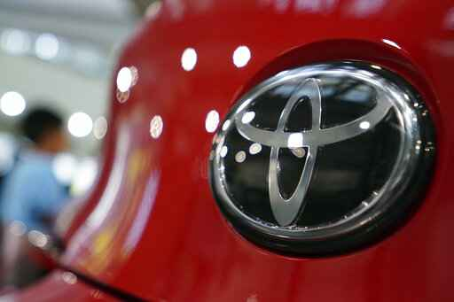 FILE - In this Aug. 2, 2019 file photo, people walk by the logo of Toyota at a show room in Tokyo.  Toyota is adding 1.5 million U.S. vehicles to recalls from early 2020 to fix fuel pumps that can fail and cause engines to stall. The company says, Wednesday, Oct. 28, 2020,  the latest recall brings the total to 3.3 million Toyota and Lexus brand vehicles that need to be repaired.  (AP Photo/Eugene Hoshiko, File)