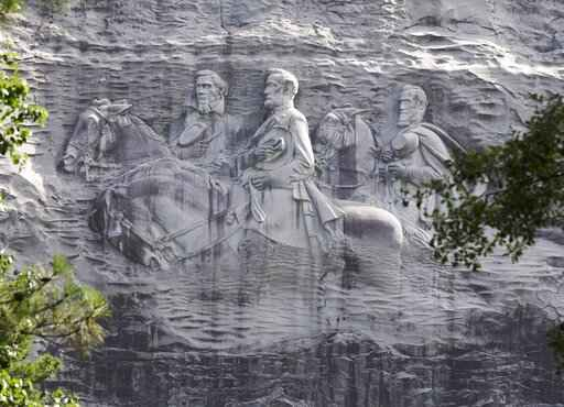 FILE - This June 23, 2015, file photo shows a carving depicting Confederate Civil War figures Stonewall Jackson, Robert E. Lee and Jefferson Davis, in Stone Mountain, Ga. The sculpture is America's largest Confederate memorial. The suburban Atlanta park that's home to the massive carving of Confederate leaders says it will close its gates Saturday, Aug. 15, 2020, in the face of a planned right-wing rally. (AP Photo/John Bazemore, File)