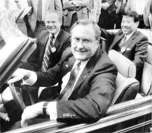 FILE - In this Oct. 7, 1985 file photo, Illinois Gov. James R. Thompson, behind the wheel of a Chrysler convertible, is joined by G. Glenn Gardner, left, and Yoichi Nakane, after a news conference in Chicago.   Thompson, known as