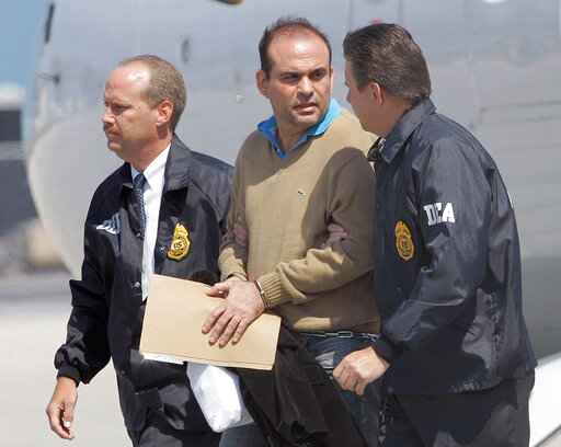 FILE - In this May 13, 2008 file photo, Colombian paramilitary warlord Salvatore Mancuso is escorted by U.S. DEA agents upon his arrival to Opa-locka, Florida. A legal battle is quietly brewing in the U.S. in 2020 over Colombia's request that this former paramilitary warlord be sent home after completing his drug sentence in the U.S. (AP Photo/Alan Diaz, File)
