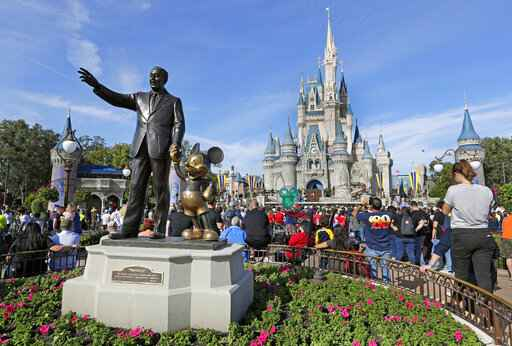 FILE - In this Jan. 9, 2019, file photo, guests watch a show near a statue of Walt Disney and Micky Mouse in front of the Cinderella Castle at the Magic Kingdom at Walt Disney World in Lake Buena Vista, Fla. Disney Plus says it hit more than 10 million sign-ups on its first day of launch, far exceeding expectations. Disney�s mix of Marvel and Star Wars movies and shows, classic animated films and new series appears to be a hit out of the gate after its launch on Tuesday, Nov. 12. (AP Photo/John Raoux, File)