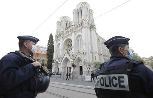 Police officers stand guard near Notre Dame church in Nice, southern France, Thursday, Oct. 29, 2020. An attacker armed with a knife killed at least three people at a church in the Mediterranean city of Nice, prompting the prime minister to announce that France was raising its security alert status to the highest level. It was the third attack in two months in France amid a growing furor in the Muslim world over caricatures of the Prophet Muhammad that were re-published by the satirical newspaper Charlie Hebdo. (Eric Gaillard/Pool via AP)