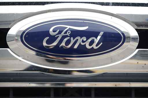 FILE - In this Oct. 20, 2019 file photograph, the company logo shines at a Ford dealership in Littleton, Colo.  Ford is recalling more than 558,000 midsize SUVs in North America because the brakes may not work properly. The recall covers certain 2015 through 2018 Ford Edge and 2016 through 2018 Lincoln MKX vehicles. Ford says in a statement Wednesday, Aug. 12, 2020,  that some front brake hoses can rupture, causing brake fluid to leak. If too much fluid leaks, it could take more effort to stop the vehicle and stopping distances could increase. (AP Photo/David Zalubowski, File)