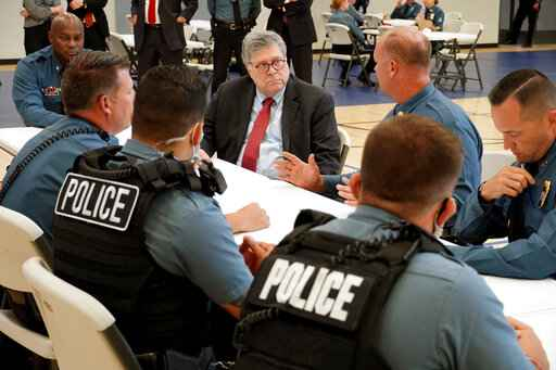 FILE - In this Aug. 19, 2020, photo Attorney General William Barr participates in a roll call with police officers from the Kansas City Police Department in Kansas City, Mo. In a private conference call this week with his U.S. attorneys nationwide, Attorney General William Barr said he wanted prosecutors to be aggressive in charging demonstrators who cause violence. (AP Photo/Mike Balsamo, File)