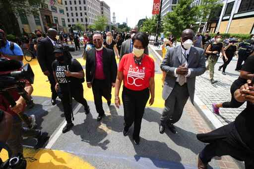 District of Columbia Mayor Muriel Bowser walks on the street leading to the White House after the words Black Lives Matter were painted in enormous bright yellow letters on the street by city workers and activists Friday, June 5, 2020, in Washington. (AP Photo/Manuel Balce Ceneta)