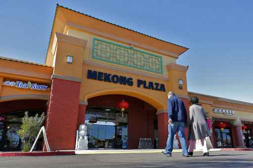 In this Feb. 13, 2020, photo, patrons enter Mekong Plaza in the Asian district, in Mesa, Ariz. Arizona's freshly crowned Asian District was deep into organizing its night market when news broke that a case of the illness known as COVID-19 was confirmed at nearby Arizona State University. Xenophobic comments on social media and phone calls started almost immediately, according to Arizona Asian Chamber of Commerce CEO Vicente Reid. (AP Photo/Matt York)