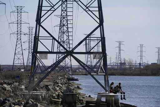 FILE - People sit at the base of a transmission tower in North Arlington, N.J., Tuesday, April 6, 2021. The Biden White House is amplifying the push for its $2.3 trillion infrastructure package with the release of state-by-state breakdowns that show the dire shape of roads, bridges, the power grid and housing affordability. Biden is scheduled to meet Monday, April 12, 2021 with Republican and Democratic lawmakers and can deploy the figures to show that his plan would help meet the needs of their constituents. (AP Photo/Seth Wenig)