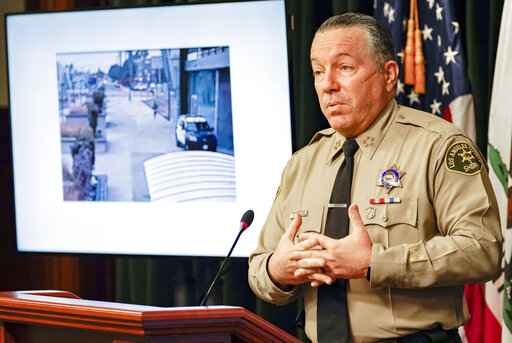 FILE - In this Sept. 17, 2020 file photo, Los Angeles County Sheriff Alex Villanueva comments on the investigation of the shooting of two deputies during a news conference at the Hall of Justice in downtown Los Angeles. A photo from surveillance video of the assault is at left. Authorities say they have arrested a man in connection with the shooting of two Los Angeles County sheriff's deputies as they sat in their squad car. Villanueva and District Attorney Jackie Lacey on Wednesday, Sept. 30, 2020 said attempted murder charges have been filed against 36-year-old Deonte Lee Murray. He was arrested two weeks ago in connection with a separate carjacking. (AP Photo/Damian Dovarganes, File)