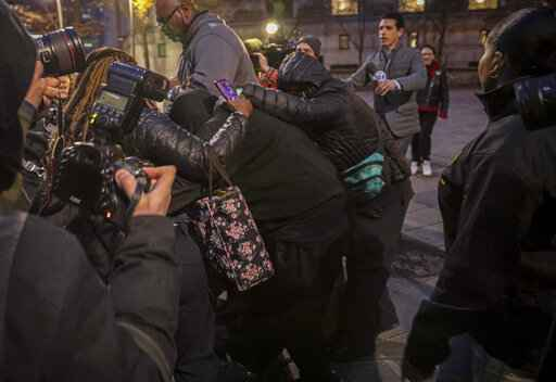 Supporters surround and hide from view one of two jail guards, center, responsible for monitoring Jeffrey Epstein the night he killed himself, following their federal court arraignment charge for falsifying prison records, Tuesday Nov. 19, 2019, in New York. (AP Photo/Bebeto Matthews)