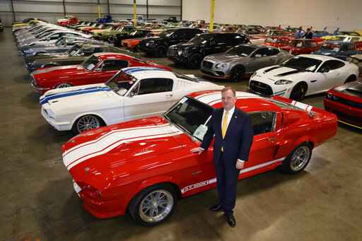 FILE - In this Sept. 16, 2019 photo, McGregor Scott, U.S. Attorney for the Eastern District of California, stands next to a 1967 Ford Shelby GT 500, that was seized along with other cars by the federal government that are now housed in a warehouse in Woodland, Calif. Two employees of a defunct San Francisco Bay Area solar energy company pleaded guilty Tuesday, Oct. 22, 2019, to participating in what federal prosecutors say was a massive $2.5 billion fraud scheme that defrauded investors of $1 billion. It�s the largest single-owner car collection ever auctioned by the U.S. Marshals Service, with vehicles to be auctioned off on Wednesday.  (Randy Pench/The Sacramento Bee via AP)