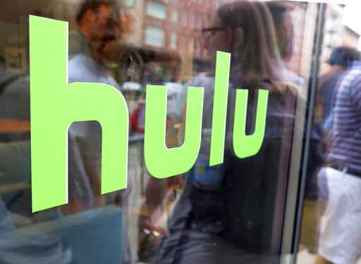 FILE - This June 27, 2015, file photo, shows the Hulu logo on a window at the Milk Studios space in New York. Hulu is again raising prices for its online TV bundle, as other streaming-TV providers do the same.