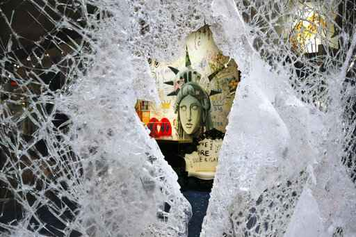 A Statue of Liberty painting is seen through a smashed Dolce and Gabbana store window, Monday, June 1, 2020, in the SoHo neighbourhood of New York. Protesters broke into the store Sunday night in reaction to George Floyd's death while in police custody on May 25 in Minneapolis. (AP Photo/Mark Lennihan)
