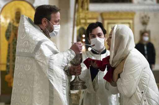 An orthodox priest wearing a face mask to protect against coronavirus distributes Holy Communion during a service at the Christ the Savior Cathedral in Moscow, Russia, Tuesday, June 2, 2020. Churches in Moscow reopen to believers after a two-month lockdown imposed to control the spread of the coronavirus. (AP Photo/Pavel Golovkin)