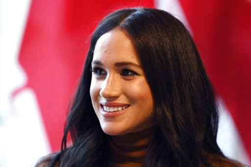 FILE - In this Tuesday, Jan. 7, 2020 file photo, Meghan, Duchess of Sussex smiles during her visit with Prince Harry to Canada House, in London. The Duchess of Sussex is seeking to delay the start of the trial in her privacy action against a British newspaper over its publication of excerpts from a
