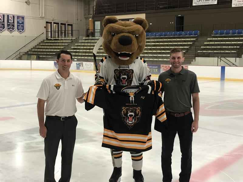 Rochester Grizzlies' head coach Casey Mignone (pictured left) poses for a photo with the team's newest jerseys with Austin Bruins' mascot