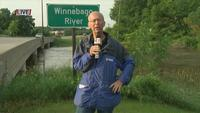 Dan Conradt reporting along the swollen Winnebago River in Forest City, IA
